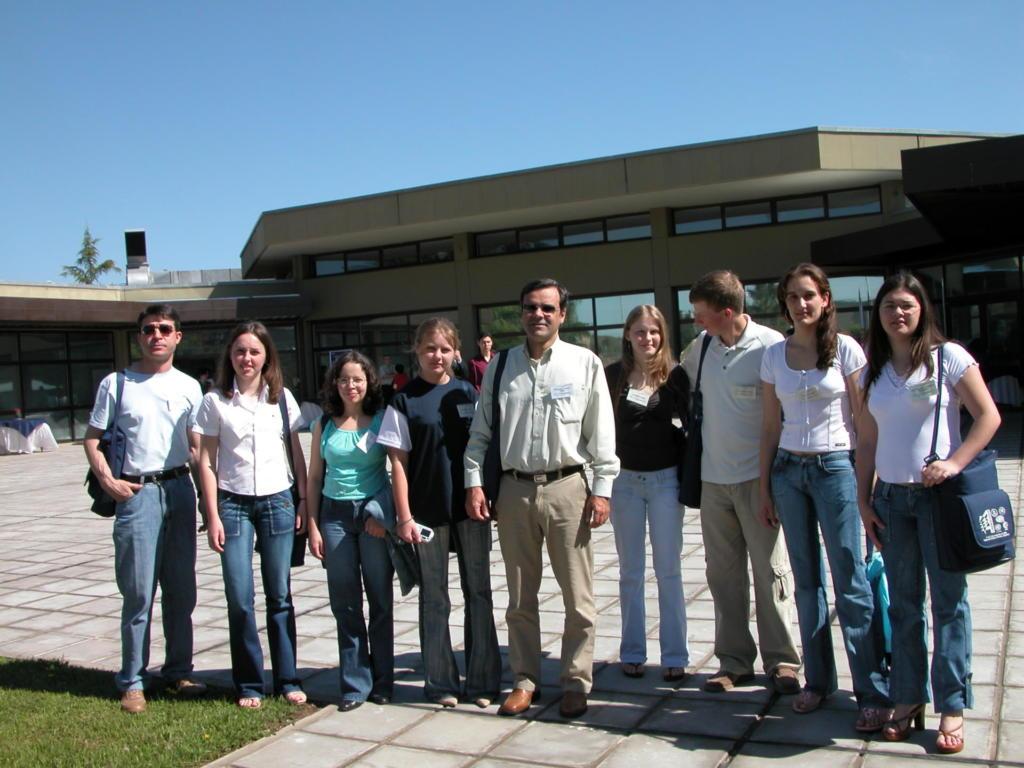 Foto horizontal com nove pessoas em pé na frente de um prédio