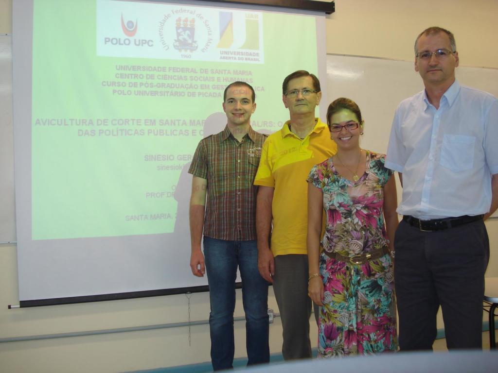 Foto horizontal com quatro pessoas em pé na frente de uma tela de projeção