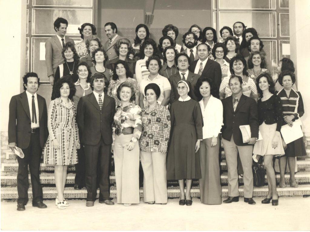 Foto horizontal em preto e branco com diversas pessoas em pé em uma escada