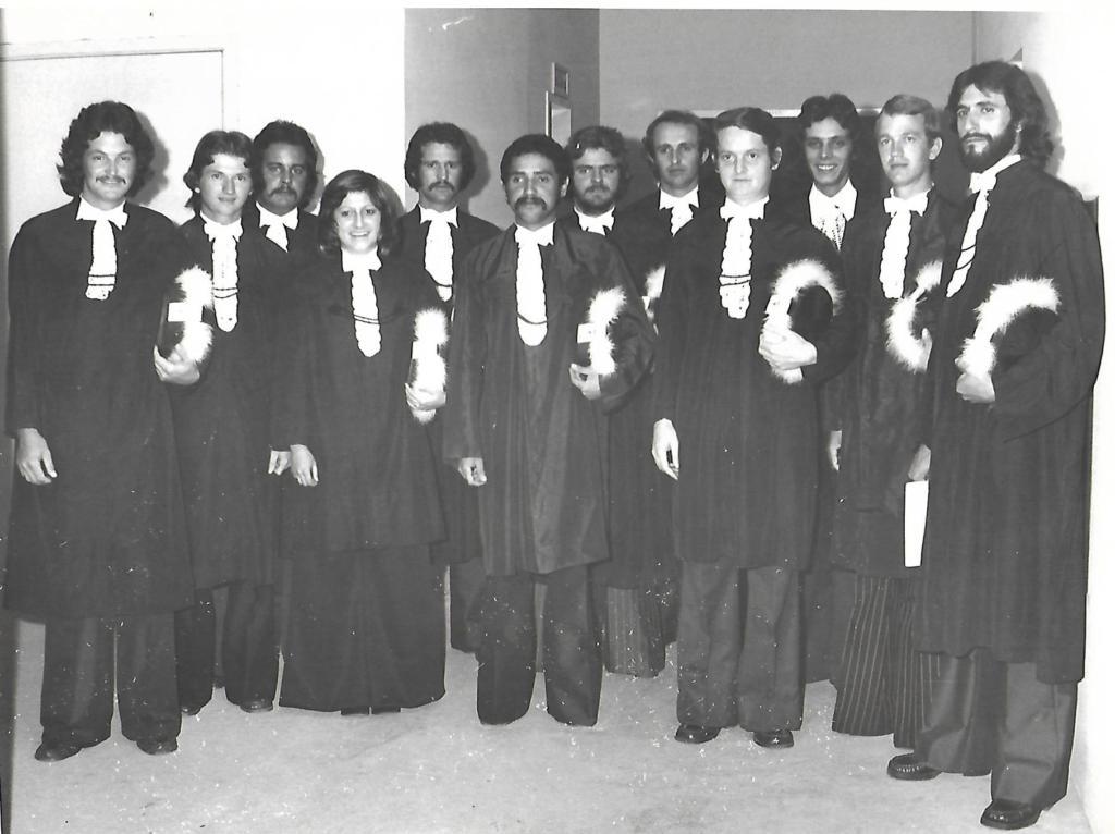 Foto horizontal em preto e branco de turma de formandos ventindo togas