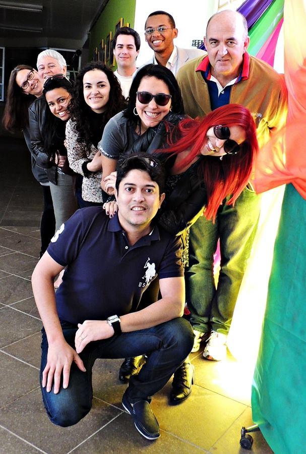 Foto vertical com algumas pessoas em pé e outras agachadas em um corredor colorido