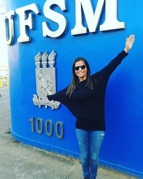 Foto vertical, mulher de braços abertos em frente ao muro azul na entrada da UFSM