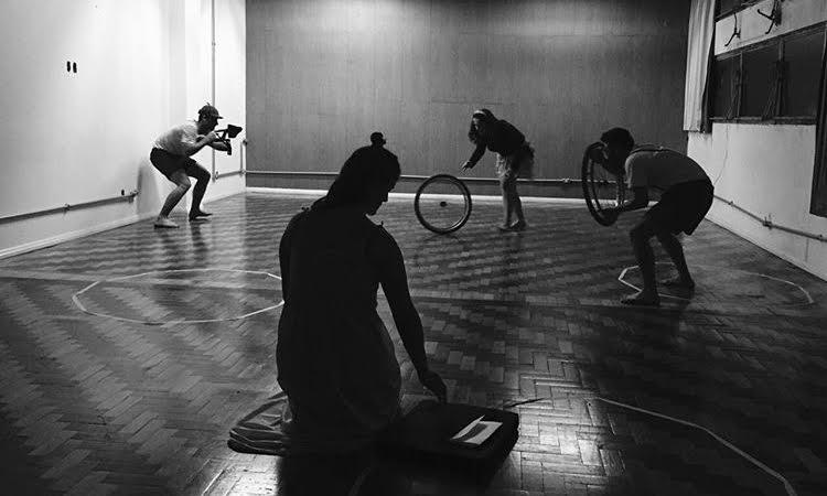 Foto em preto e branco de quatro pessoas em posições diferentes e um estúdio de teatro