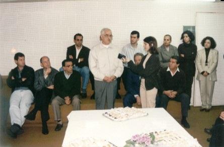 Foto horizontl com sala cheia de pessoas. Um homem e uma mulher mais à frente, o homem dando enteevista e a mulher gravando em um gravador portátil