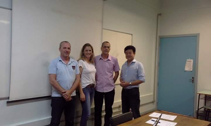 Foto horizontal com 4 pessoas em pé numa sala de aula em frente ao quadro branco