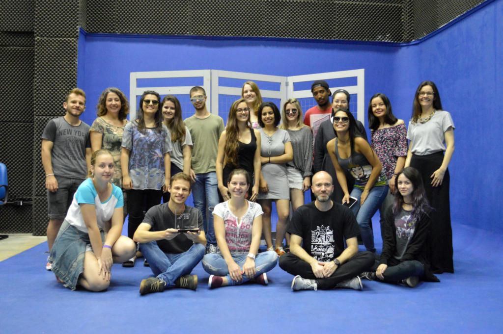 Foto horizontal, turma reunida em estúdio de TV com fundo azul, um dos estudantes segura um troféu