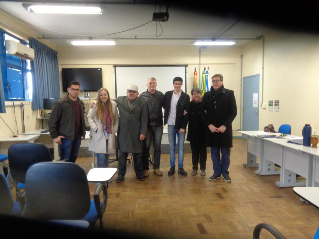 Foto horizontal com 7 pessoas em pé em uma sala de aula, quadro branco ao fundo
