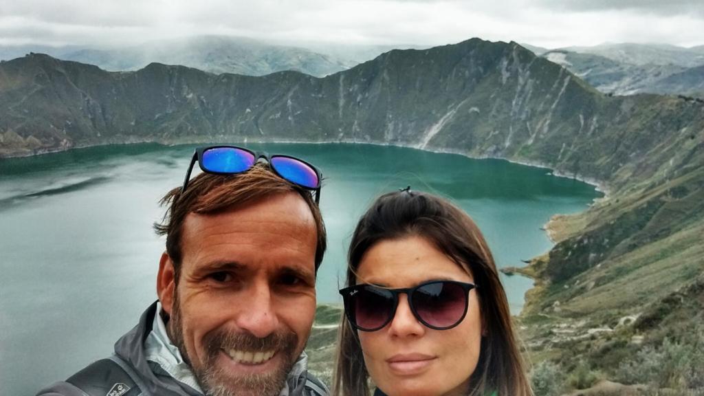 Foto em close dos rostos de um homem e uma mulher com uma paisagem ao fundo