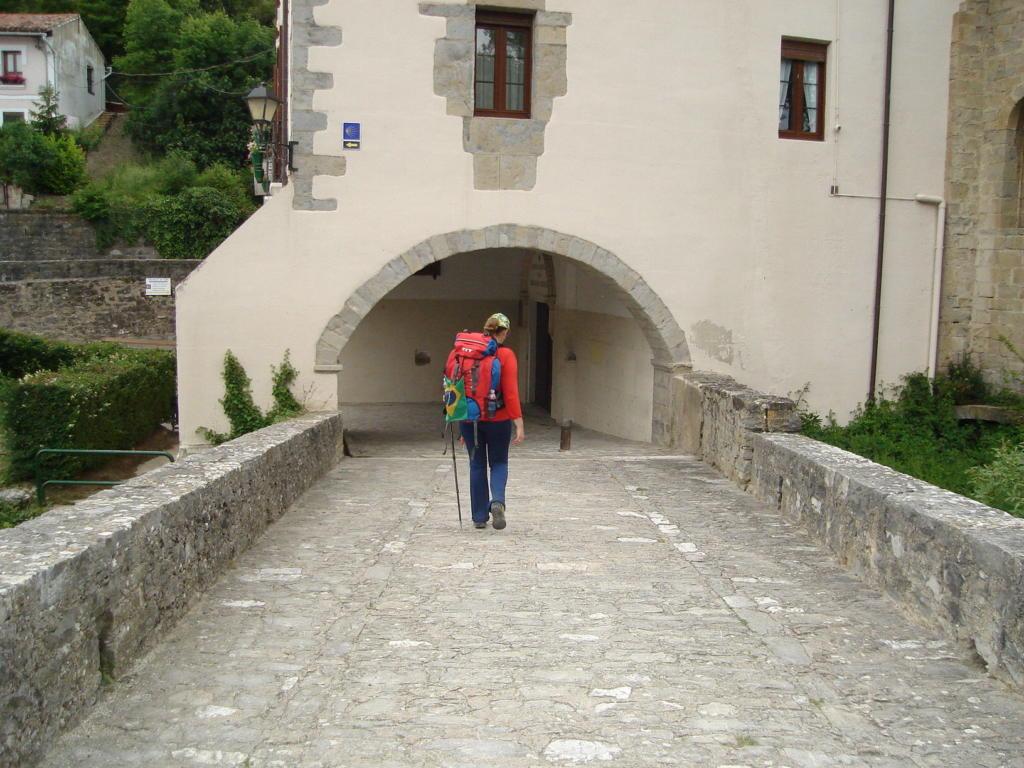 Foto horizontal, mulher de costas com mochila de viagem em uma ponte com prédio antigo ao fundo