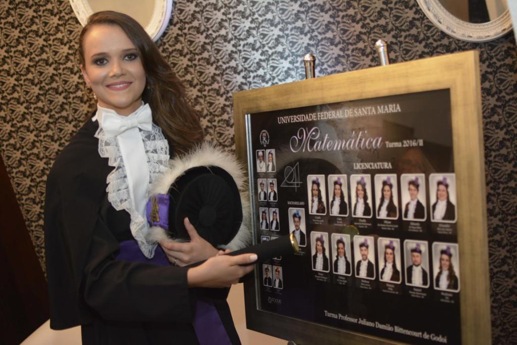 Formanda vestida com beca e segurando o capelo ao lado do quadro de formatura do curso de Matemática