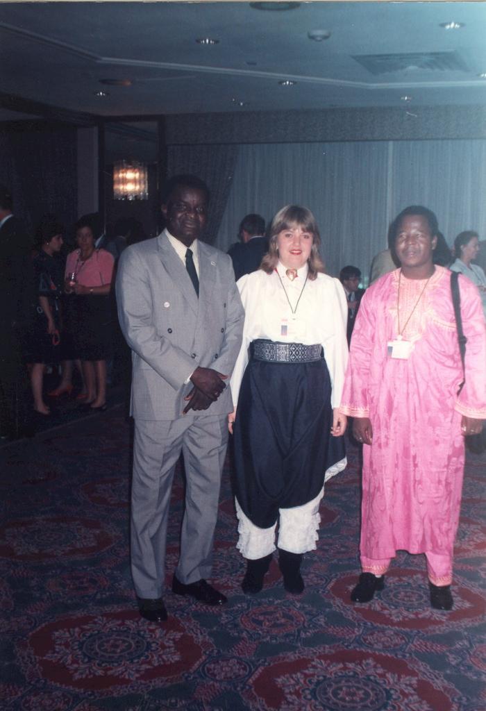 Foto vertical de três pessoas em pé vestidas com roupas típicas de seus países