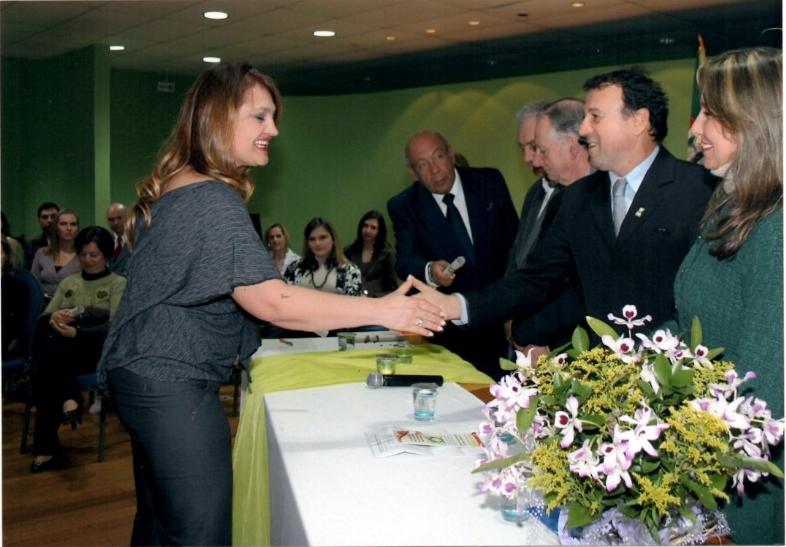 Foto horizontal de mulher cumprimentando homem por cima de uma mesa com flores