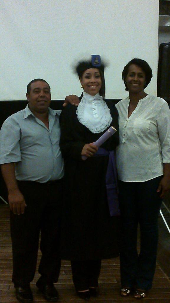 3 pessoas em pé, no meio uma formanda vestindo beca e segurando canudo de formatura