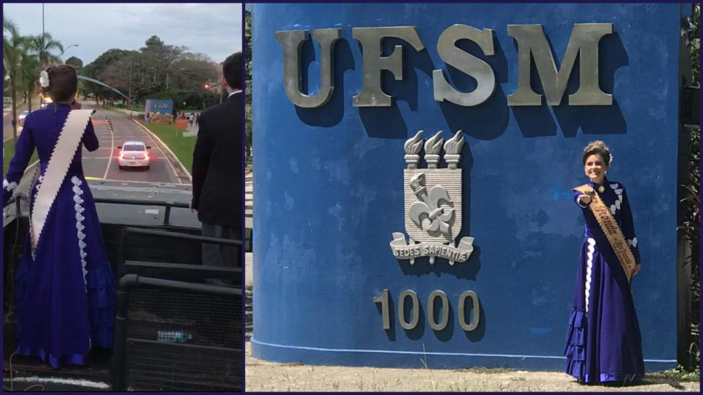 Foto horizontal de mulher vestida de prenda em frente ao muro azul de entrada da UFSM, com brasão da universidade prateado