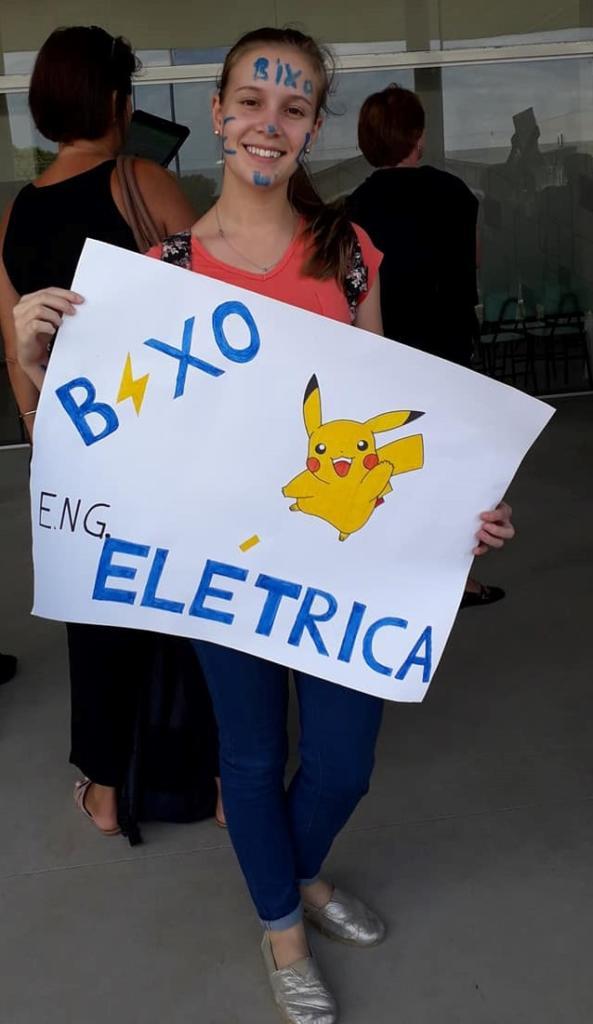 Foto vertical de menina com o rosto pitado de Bixo segurando cartaz branco dizendo Bixo Engenharia Elétrica