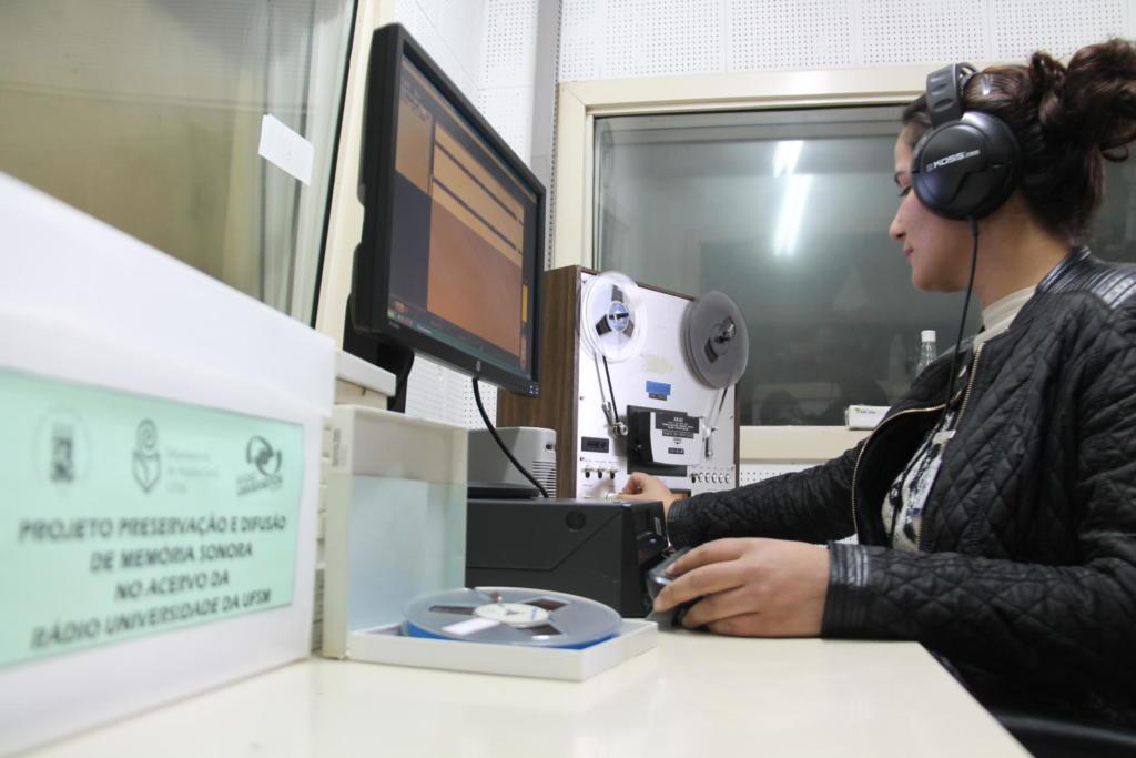 Foto horizontal de mulher sentada em laboratório em frente ao computador, usando fone de ouvido