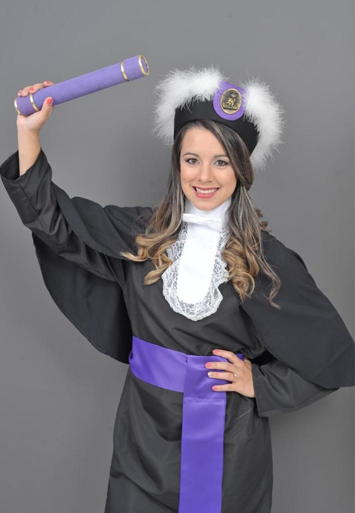 Foto verticam com uma mulher formanda vestida com beca e segurando canudo de formatura