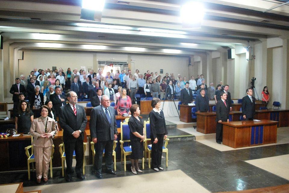 Foto horizontal com plenária da Câmara de Vereadores cheia, todas as pessoas da plateia em pé