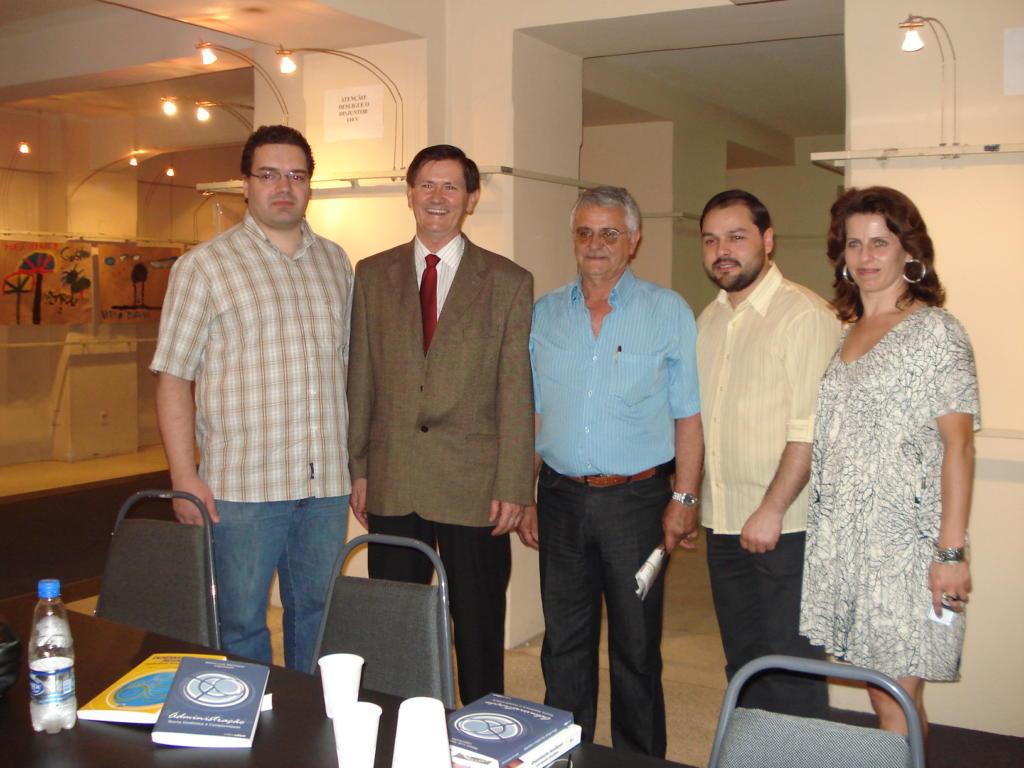 Foto horizontal, quatro homens e uma mulher em pé atrás de uma mesa de reuniões