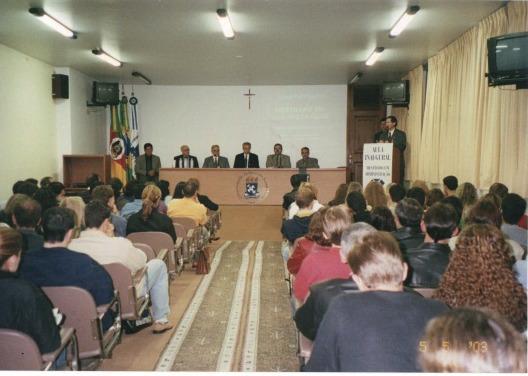 Foto horizontal, auditório cheio. Ao fundo palco e mesa com 6 pessoas sentadas e uma pessoa falando no púlpito