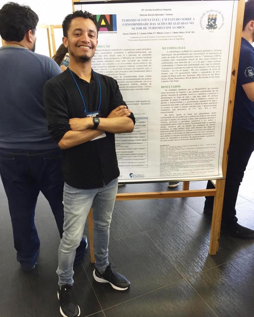 Estudante em pé na frente de um banner da JAI