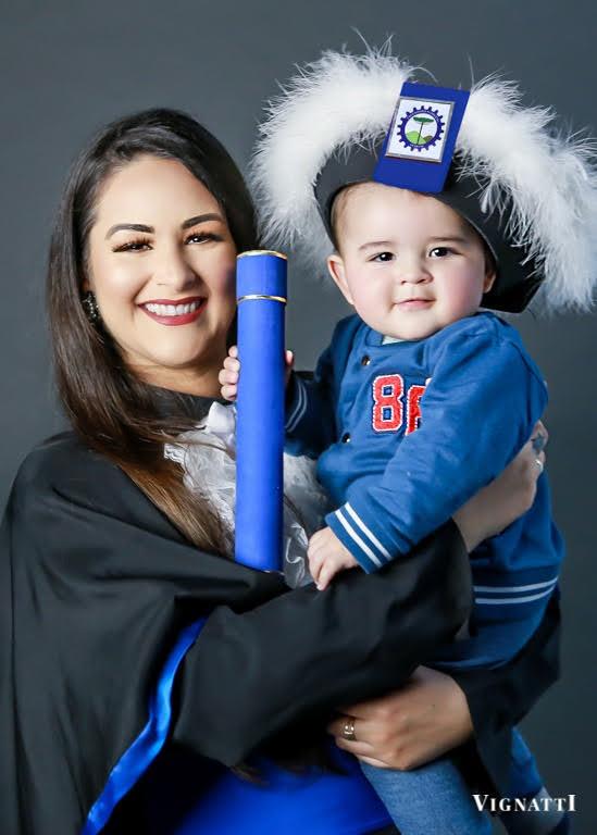Formanda mulher vestindo beca e segurando bebê menino no colo vestindo capelo