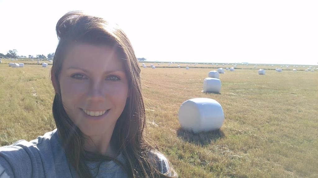 Foto horizontal selfie de aluna com campo ao fundo