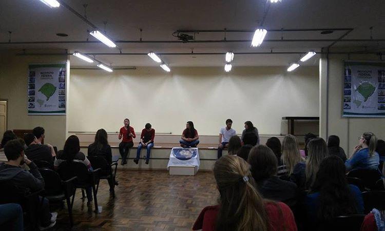 Foto horizontal com auditório cheio e 5 estudantes sentados no palco falando