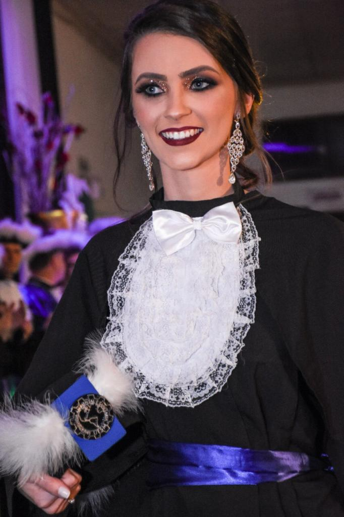 Foto vertical de formanda vestida com beca e segurando capelo