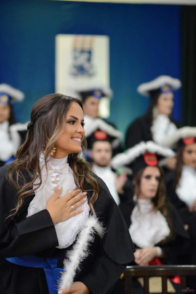 Estudante mulher em dia de formatura vestindo beca e segurando capelo, com turma de formandos ao fundoo