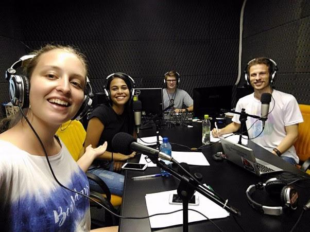 Foto horizontal em estúdio de rádio, alina em primeiro plano com mais 3 pessoas sentadas ao fundo