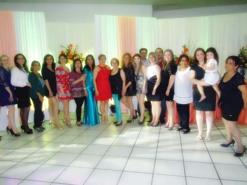 Foto horizontal com diversas mulheres em pé em um salão de festas