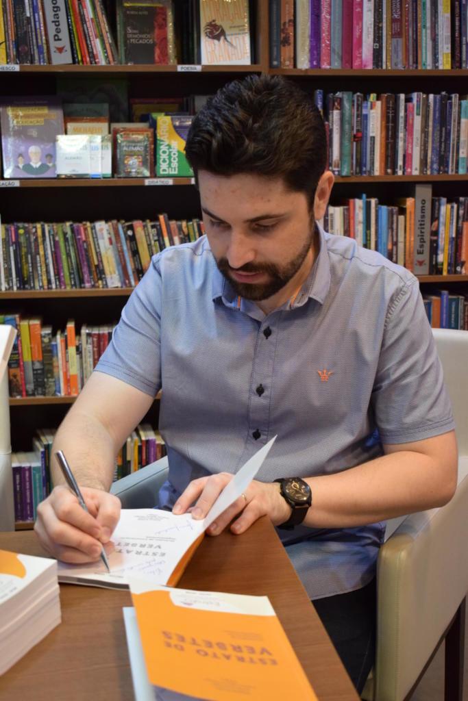 Foto vertical de homem sentado assinando um livro. Ao fundo, uma prateleira cheia de livros