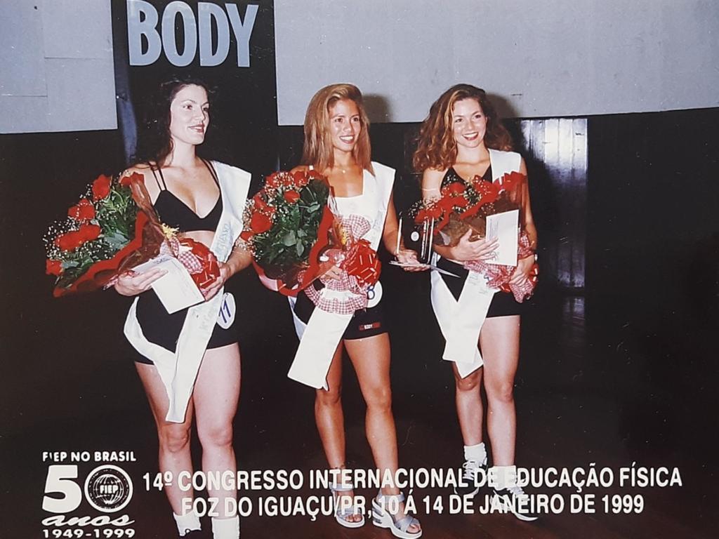 Foto horizontal de três meninas em pé, usando shorts e top pretos, faixas de rainha de evento e segurando buquê de rosas vermelhas