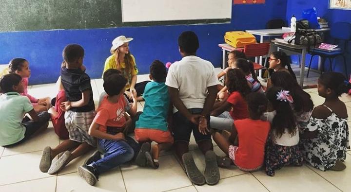 Foto retangular horizontal de diversas crianças sentadas no chão em torno de uma professora