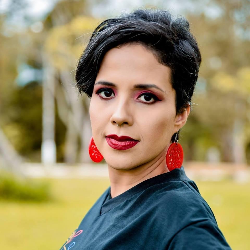 Foto quadrada colorida de rosto de mulher vestindo camiseta preta, cabelos curtos pretos, batom e brincos vermelhos