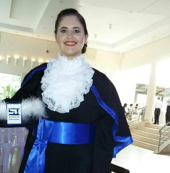 Foto vertical colorida de formanda vestindo beca e segurando capelo