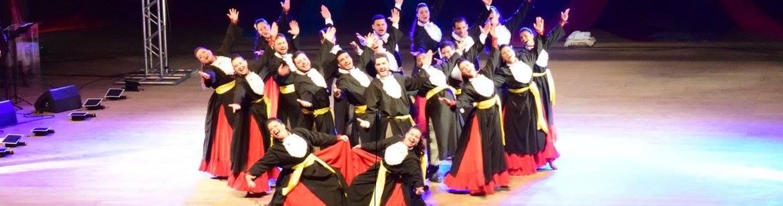 Foto horizontal colorida com 20 dançarinos vestidos de beca de formatura em palco