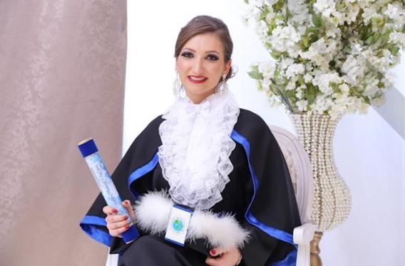Foto quadrada colorida de formanda vestindo beca de formatura e segurando canudo