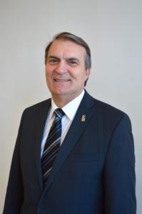 Foto do reitor Paulo Burmann sorrindo, veste camisa branca, blazer e gravata azul marinho