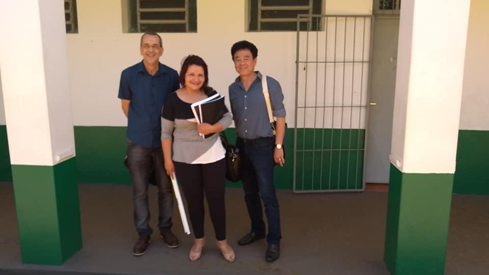 Dois homens e uma mulher em pé em frente a portão de escola