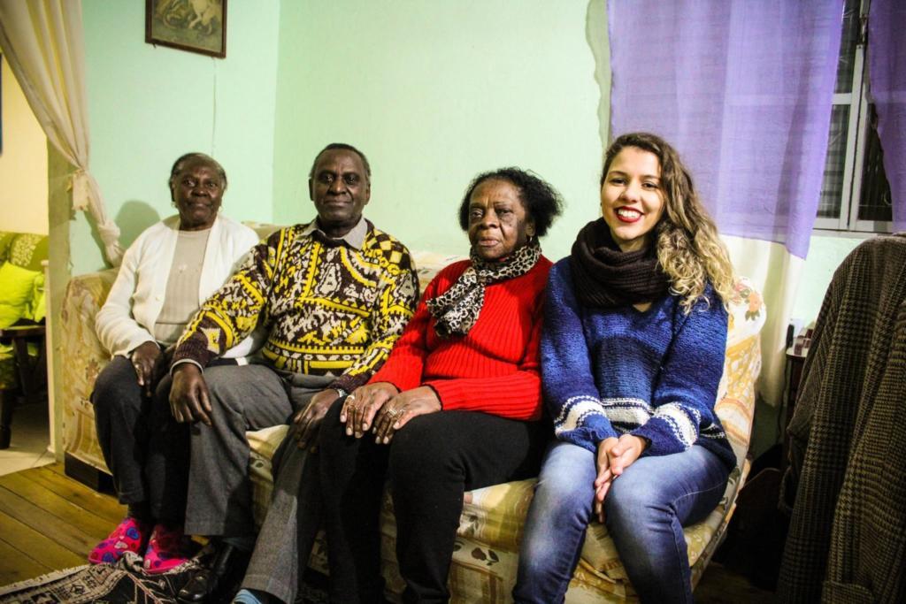 Foto de 4 pessoas sentadas no sofá de uma casa. 3 negros idosos e uma jovem estudante
