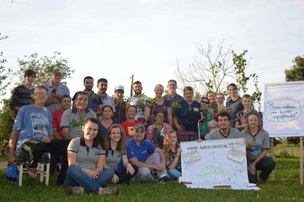 Grupo de pessoas posando pra foto no campos, algumas seguram cartazes