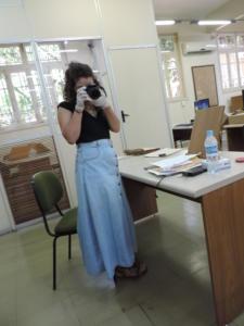 Mulher em pé no Arquivo Público do Estado do Rio Grande do Sul (APERS), 28 de janeiro de 2020 usando luvas e segurando uma máquina fotográfica. Foto Vanessa Flores dos Santos.