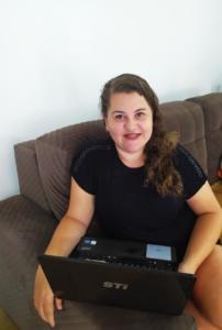 Foto de mulher sentada no sofá com notebook no colo