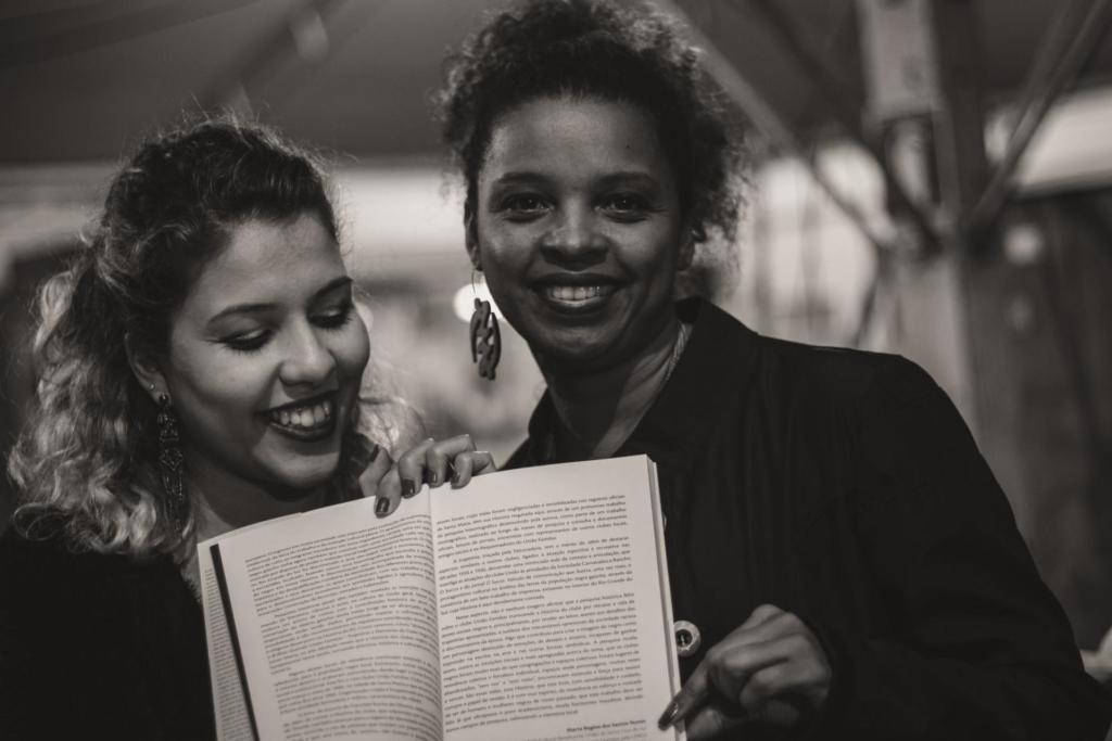 Foto preto e branco de duas mulheres segurando um livro aberto