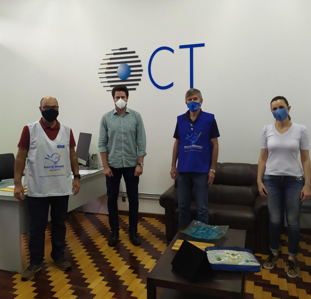 Foto colorida mostra quatro pessoas de máscara, distantes, posando para foto, na frente de uma parede branca com o logo do CT pintado