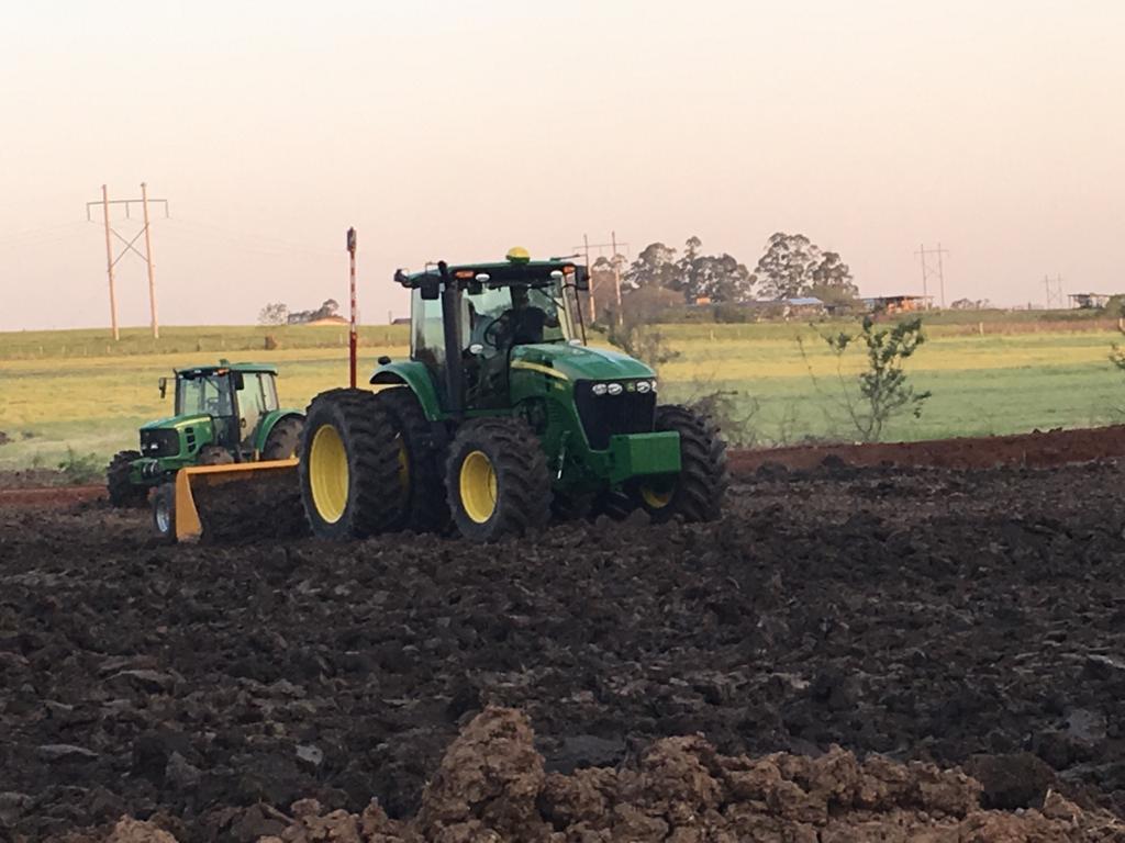 Foto colorida mostra um trator verde mais à frente, outro logo atrás, arando uma área de terra