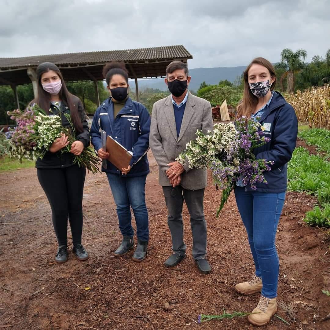 foto colorida mostra quatro pessoas, três mulheres e um homem, em um lugar ao ar livre, duas tem flores nas mãos, todos usam máscaras. Eles estão lado a lado e posam para a foto
