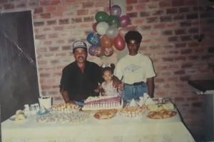 Foto colorida de três pessoas em uma sala. Uma criança ao centro, com um homem do lado direito e uma mulher do lado esquerda. Na frente deles, uma mesa com comidas e um bolo de aniversário.